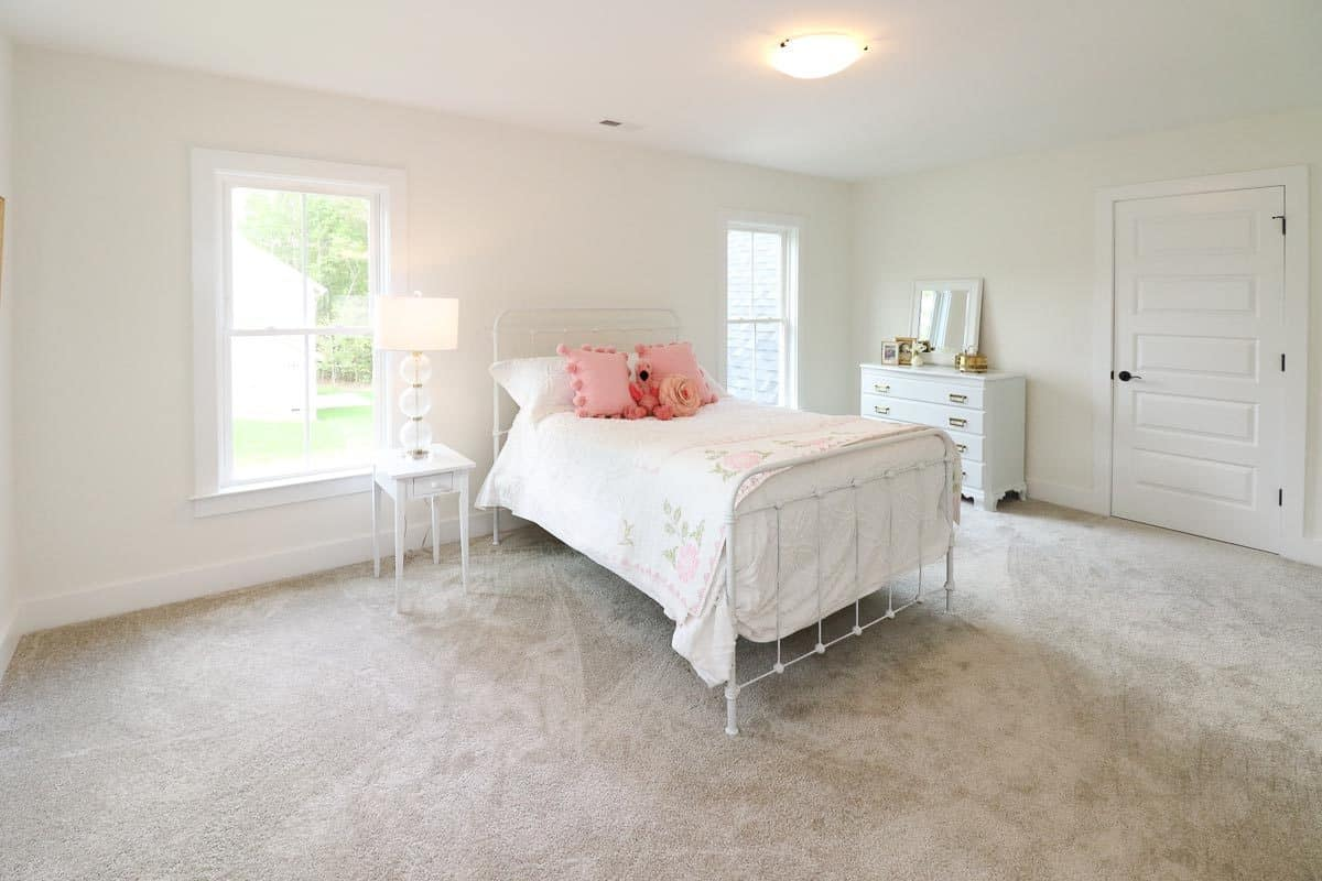 This girl's bedroom offers a metal bed, white dresser, and a small nightstand topped with a drum table lamp.