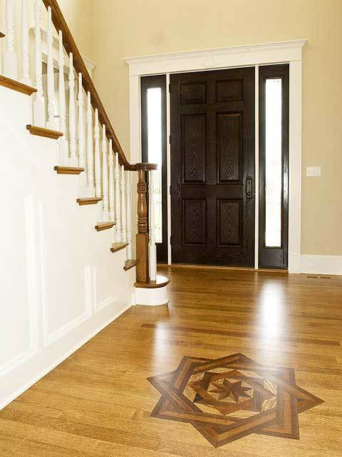 The foyer has a dark wood front door, a traditional staircase, and a natural hardwood flooring adorned with a star decal.