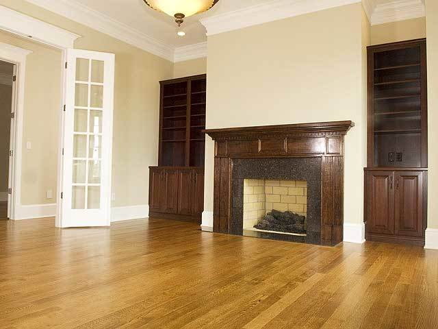 The family room features a brick fireplace flanked by wooden built-in shelves and base cabinets.