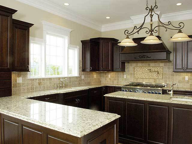 The kitchen offers dark wood cabinets, a matching center island, and granite countertops.