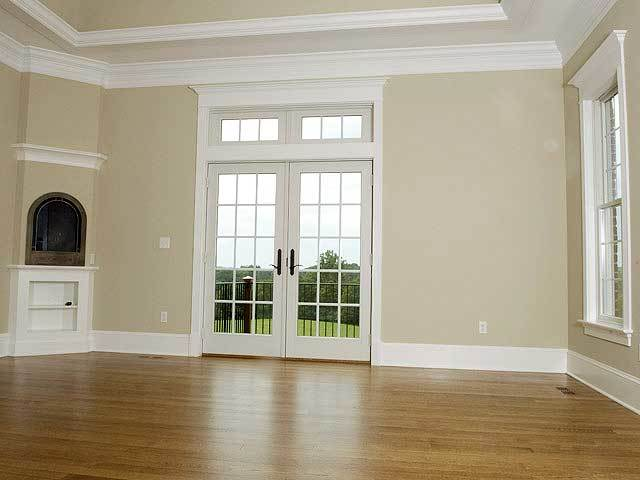 The primary bedroom showcases a tray ceiling and a french door leading out to the balcony.