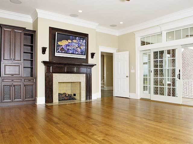 Family room with a fireplace and wall-mounted TV fixed next to the dark wood cabinet.