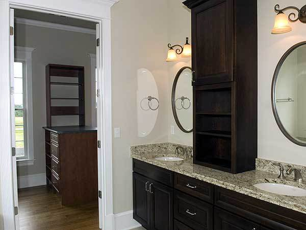 The primary bathroom has a dual sink vanity and a white door that opens to the walk-in closet.