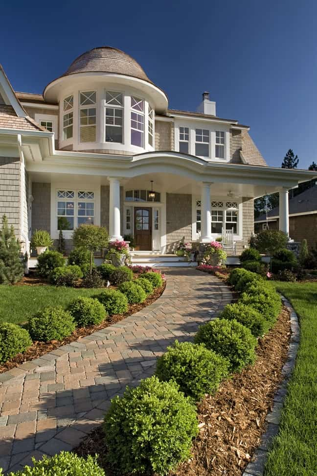 Stone brick paving flanked by manicured shrubs leads to the home's porch that's supported by decorative columns.