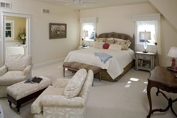 Primary bedroom with cozy seats and a printed bed paired with distressed nightstands.