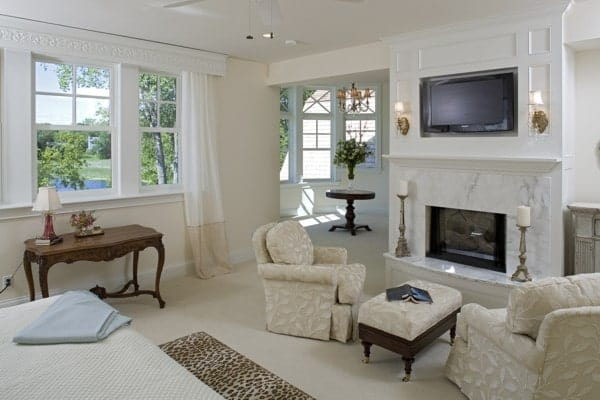 The sitting area by the fireplace offers skirted seats and a matching ottoman over beige carpet flooring.
