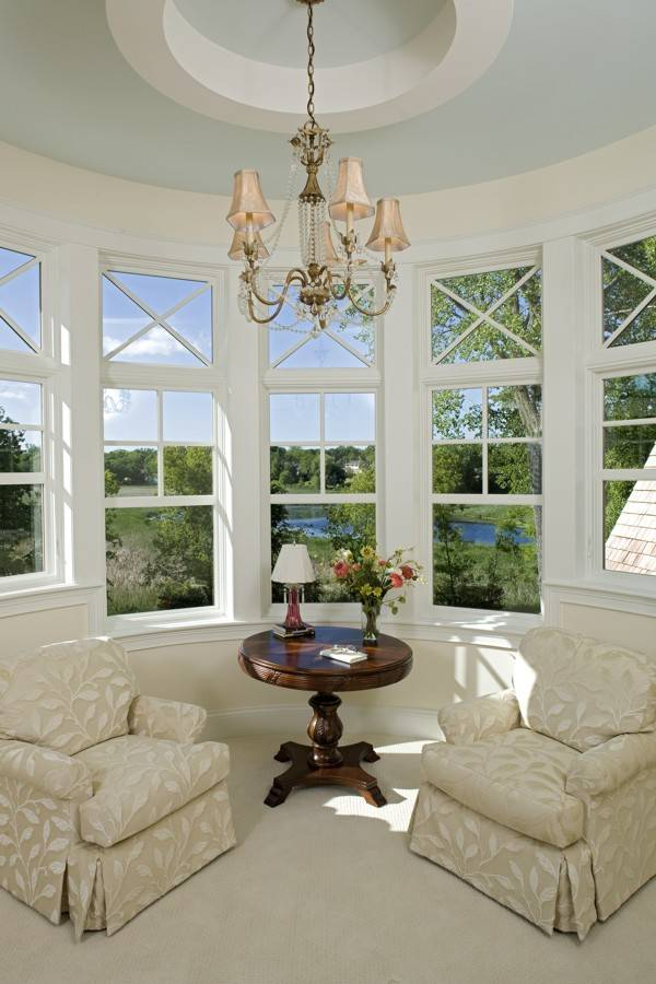 A sitting room inside the primary bedroom with white framed windows and a round tray ceiling mounted with a beaded chandelier.