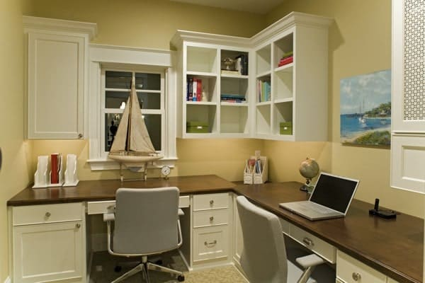 The home office is filled with built-ins and wooden desks paired with gray swivel chairs.