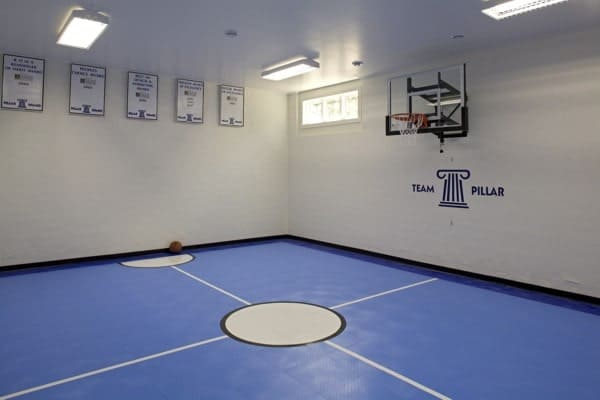 Sport court with blue flooring and white walls matching with the ceiling that's mounted with cool lamps.