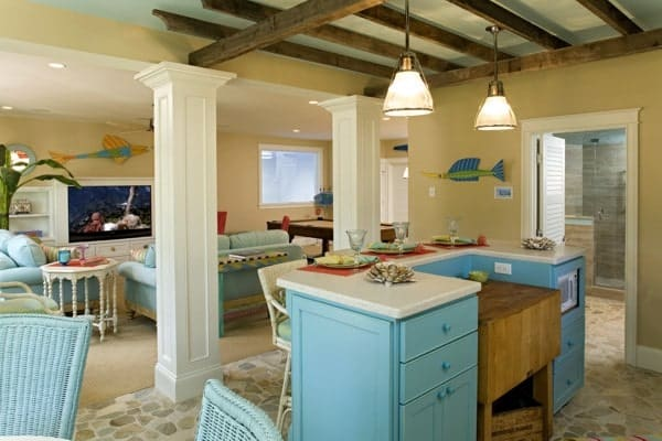 Wet bar lined with interior columns and filled with a blue island bar under the beamed ceiling.