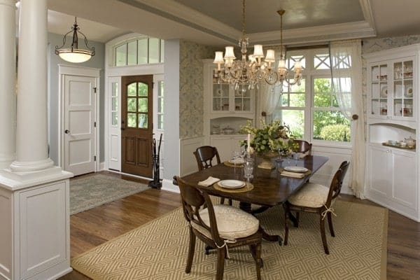 Formal dining room with white display cabinets and a dark wood dining set sitting over the brown textured rug.
