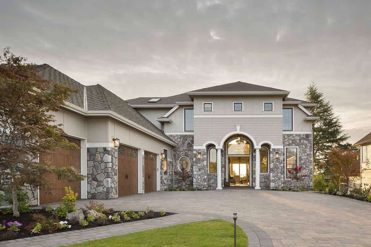 A closer look shows the brick cladding, stone accents and decorative columns framing the front porch.