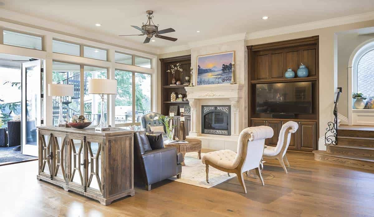 Great room with a mirrored console table, tufted seats, TV, and a classy fireplace topped with a landscape painting.