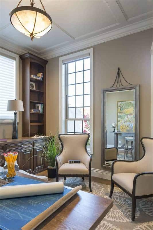 The home office is filled with wooden furniture and a full-length mirror fixed against the beige wall.