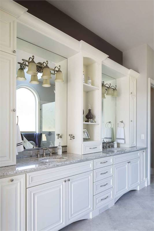The large vanity is fitted with his and her sinks and frameless mirrors mounted with glass sconces.