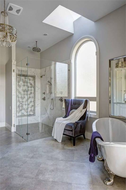 The other side view of the primary bathroom shows the walk-in closet, beaded chandelier, and a skylight on top of the velvet chair.