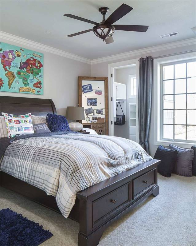 This bedroom has carpet flooring and a white framed window covered in gray draperies.