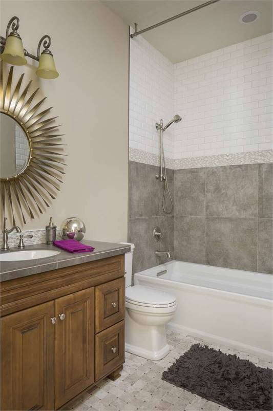 This bathroom is equipped with a tub and shower combo, a toilet, and a sink vanity paired with a stylish suburst mirror.