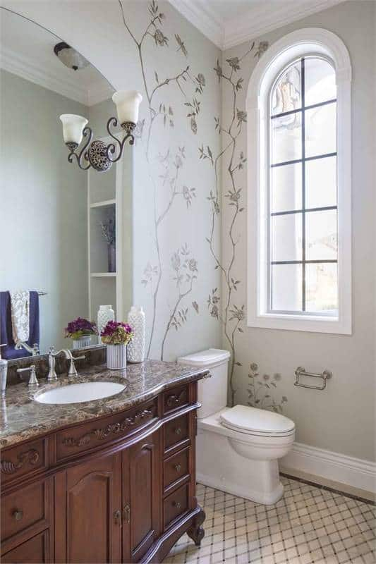Smaller bathroom with a toilet, granite top vanity and an arched window.