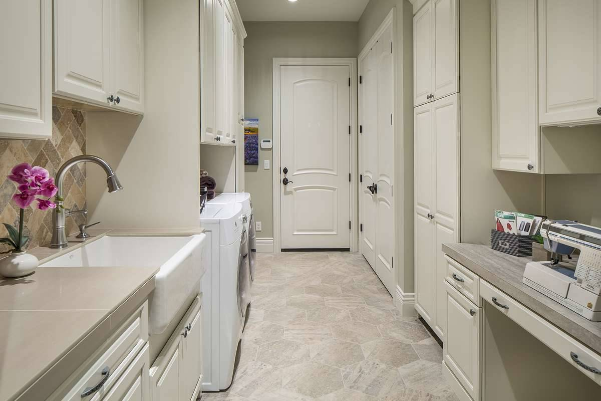 Laundry room with hex tile fflooring and white cabinets fitted with wrought iron hardware.