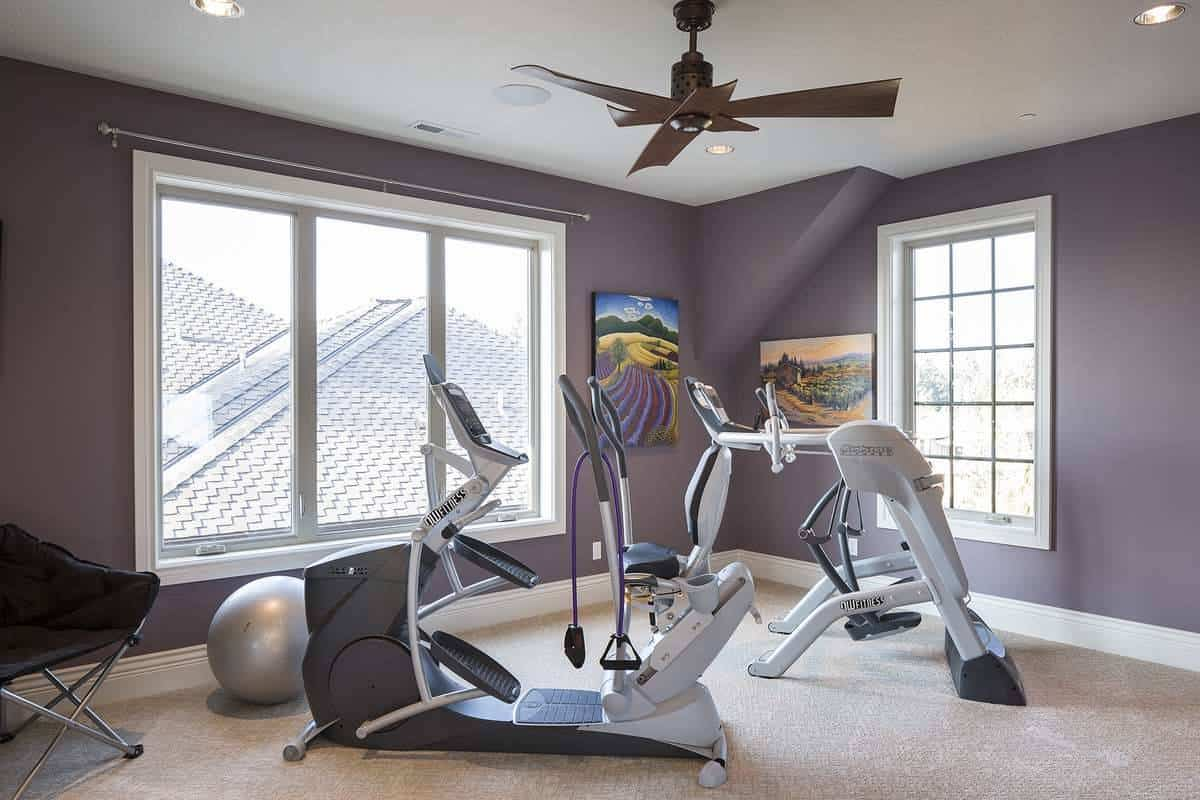 Exercise room with carpet flooring and purple walls adorned by colorful landscape artworks.