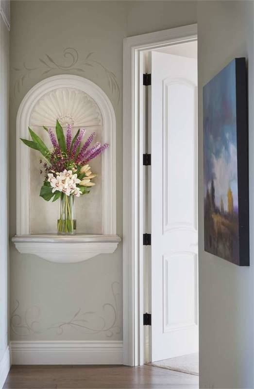 The hallway is decorated with a lovely painting and an arched inset filled with gorgeous flowers.