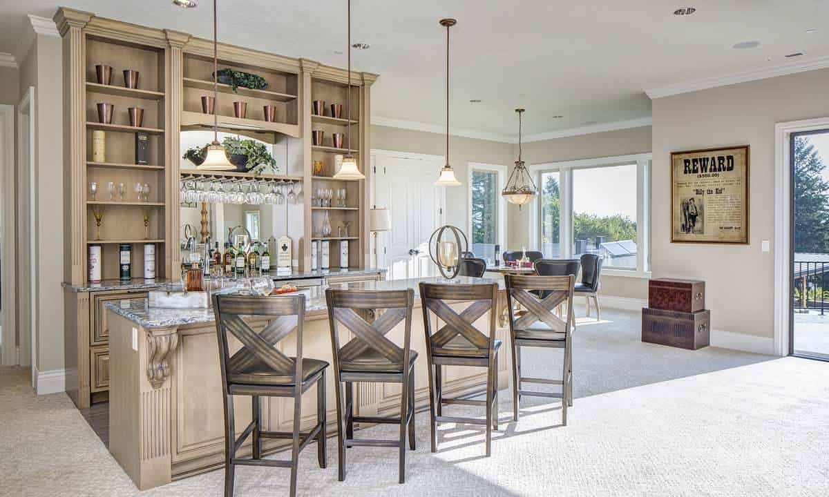 Spacious game room with a bar showcasing wooden shelves and cabinets along with a granite top counter complemented with dark wood chairs.
