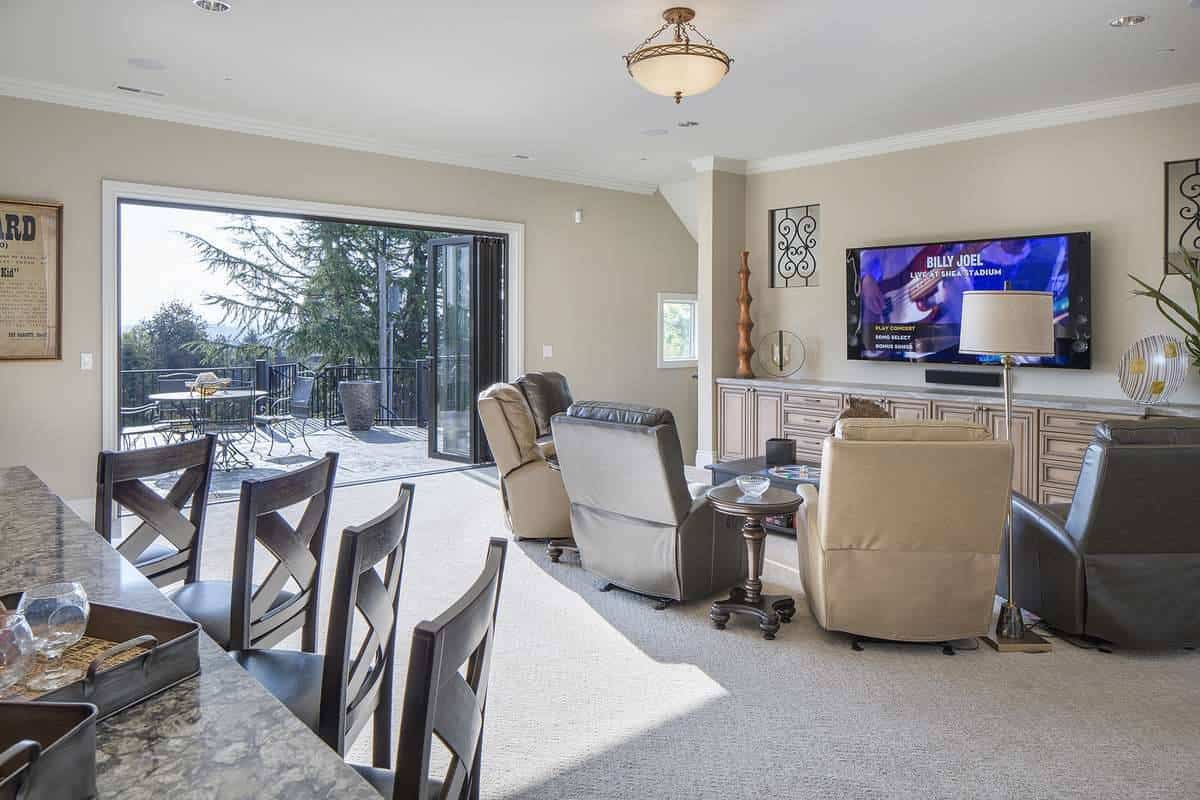 Across is the media room with cozy recliners and a folding glass door that opens out to the balcony.