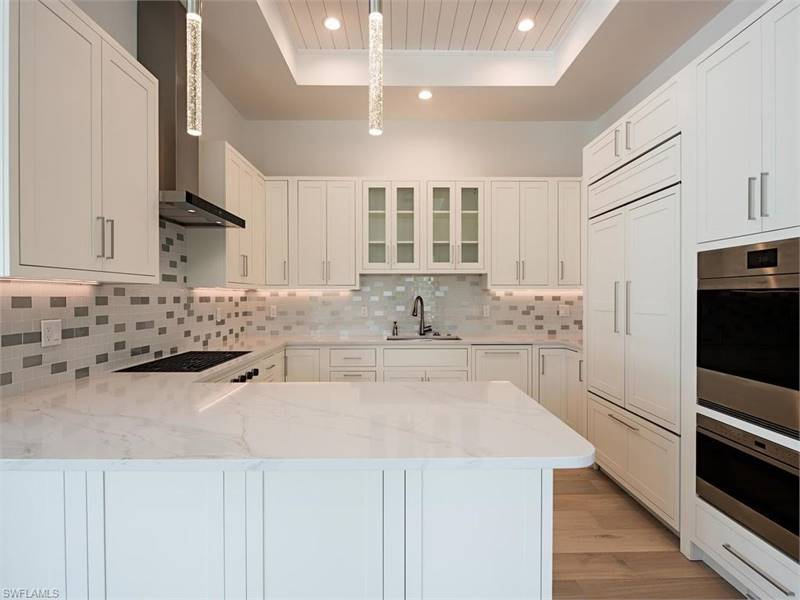 The kitchen is equipped with cutting-edge appliances, white cabinetry, and a peninsula with marble countertop.