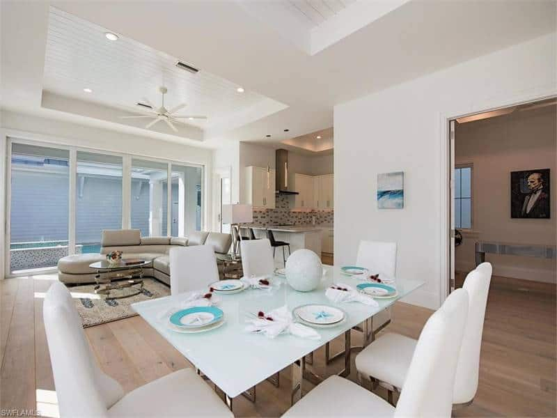 A closer look at the dining area shows the white upholstered chairs and a glass dining table topped with starfish dinnerware.