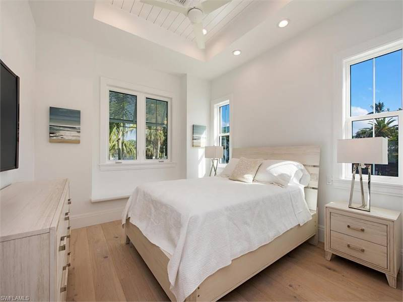 This bedroom offers a TV and light wood furniture that blends in with the wide plank flooring.