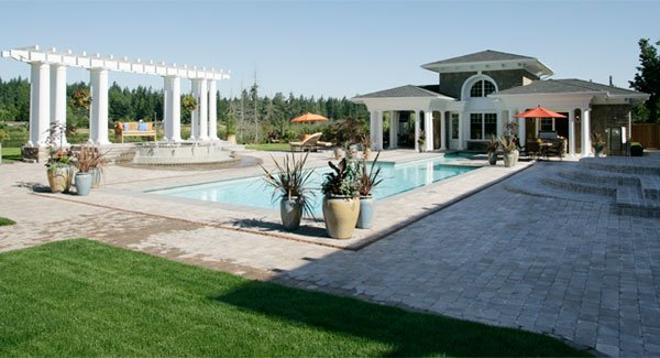 Outdoor space at the back with a sparkling pool, white pergola, and a clubhouse.
