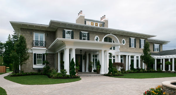 Home's facade with stone brick cladding, white-framed windows, and a front porch supported by white exterior columns.