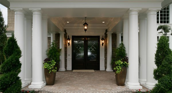 Front porch with tall potted plants and a double entry door illuminated by warm sconces and a matching pendant.