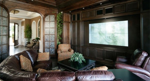 The french door opens to the media room with wood-paneled walls and brown recliners paired with a dark wood center table.