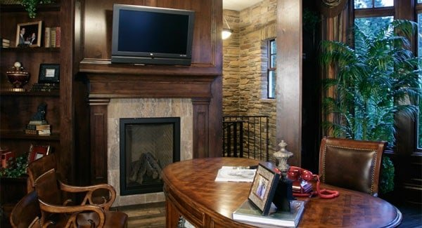 Opposite side view of the office shows the fireplace and a TV mounted on the wood-paneled pillar.
