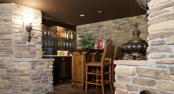Bar with glass front cabinets and a wooden counter surrounded by brick walls.
