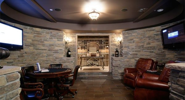 Game room in front of the white cellar with a round tray ceiling and brick walls mounted with TVs.