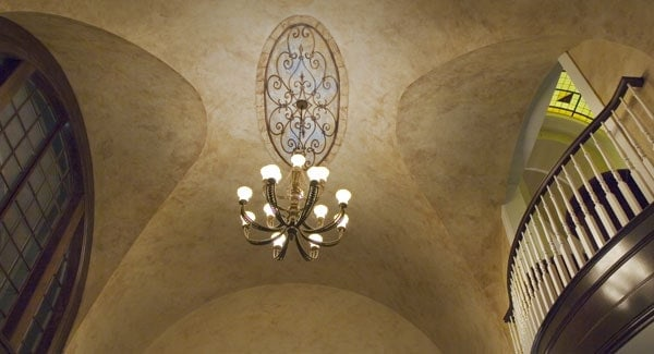The groin vault ceiling has an oval medallion with a hanging chandelier illuminating the area.