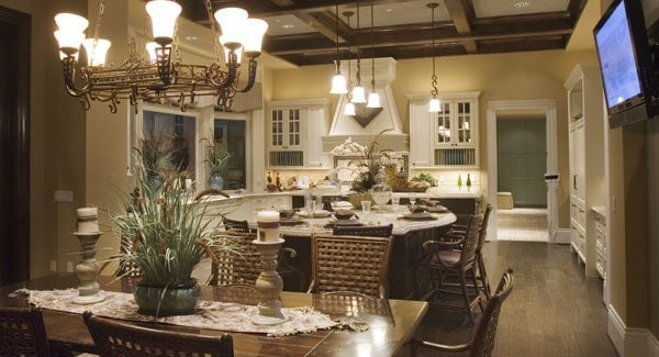 Eat-in kitchen with white cabinets and a wooden dining set under the wrought iron chandelier.
