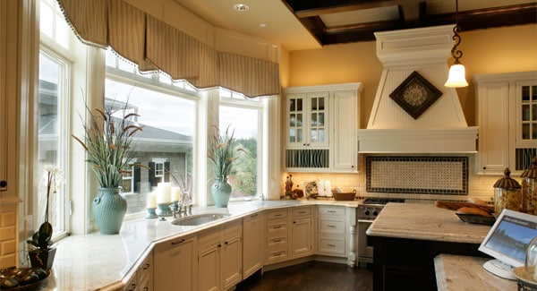 This view shows the undermount sink and glass-paneled windows dressed in striped valances.