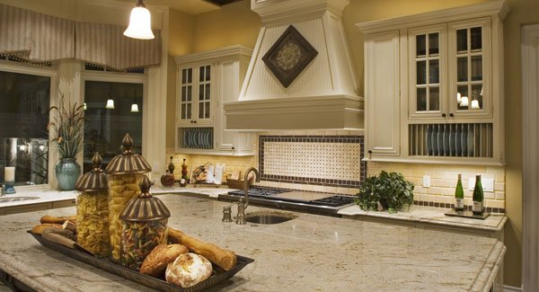 The kitchen's cooking range is paired with a bespoke vent hood flanked by glass front cabinets.