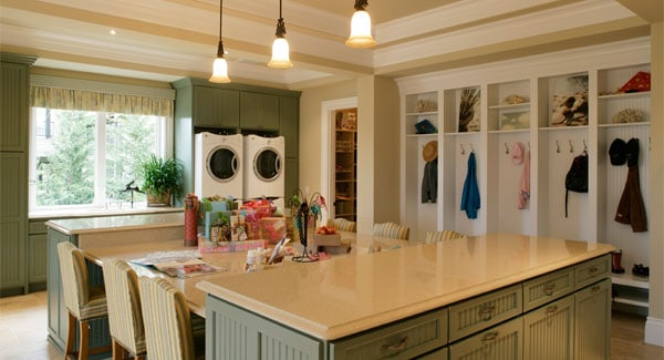 Crafts room with built-in shelves and lots of counter spaces complemented by striped cushioned chairs.