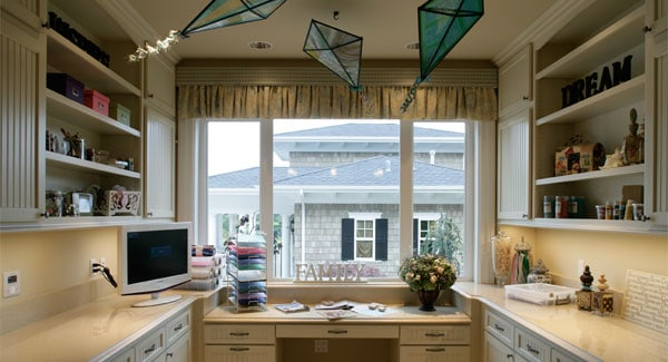 The home office across the crafts room is filled with built-in cabinets, shelves, and a desk fixed under the white-framed windows.