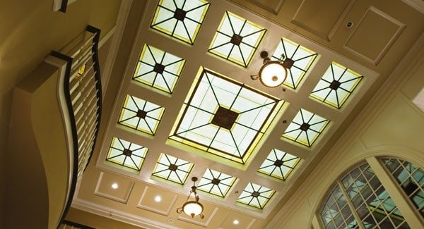 A soaring coffered ceiling fitted with decorative skylights and recessed lights.