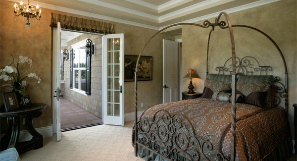 This bedroom showcases a french door and a metal canopy bed dressed in brown patterned bedding.
