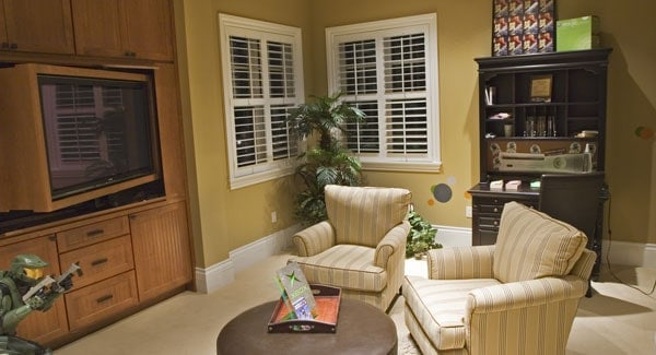 Family room with a TV, dark wood desk, and striped armchairs paired with a round coffee table.