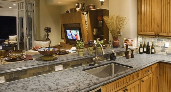 A closer view of the bar shows the two-tier granite countertops and a sink paired with a gooseneck faucet.