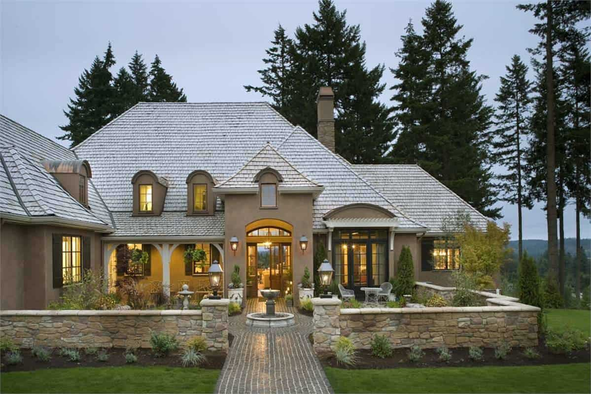 Home's front view with arched dormer windows, a warm portico, stone fence and a fountain that serves as an elegant focal point.