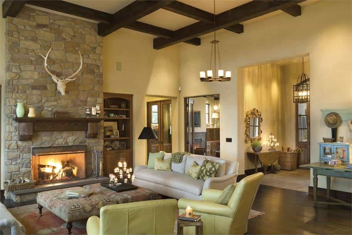 The great room has a coffered ceiling, leather seats, and a stone fireplace adorned with an antler decor.